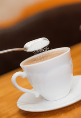 pour sugar to milk coffee of classical white cup