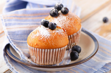 Muffins with fresh blueberries on a  wooden table