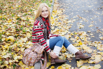 young blond woman sitting on yellow leaves in the park