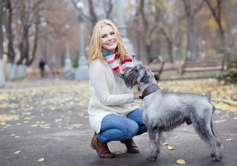 young beautiful girl with her dog mittelschnauzer in autumn park