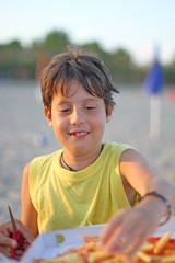 boy while eating pizza takeaway in Sunset Beach