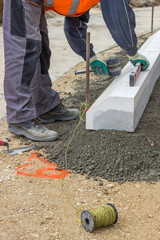 worker installing concrete curb stone and using string