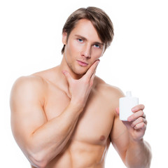 Young handsome man applying lotion.