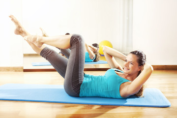 Young woman making fitness exercises stretching