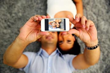 Couple making selfie photo on smartphone. Focus on smartphone