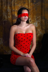 Pretty woman with blindfold sitting in dark room