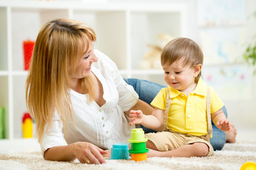 little child and woman playing  with toys