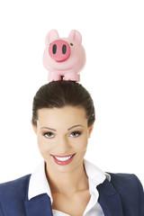 Businesswoman holding a piggybank on head