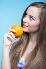 Beautiful girl with orange on the blue background