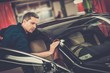 Leinwandbild Motiv Man worker polishing car on a car wash