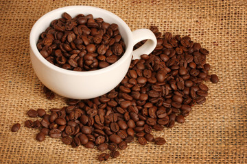 Coffee beans in white cup on brown sack background