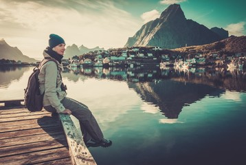 Woman sitting on a pier in Reine village, Norway