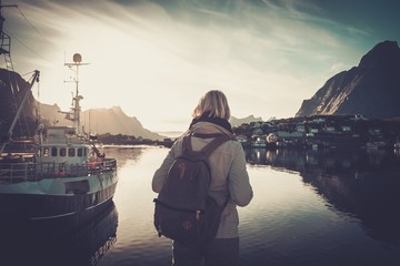 Woman traveler looking at sunset in Reine village, Norway