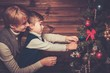 Happy mother and her lIttle boy in Christmas interior