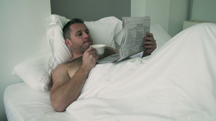 Man reading newspaper and drinking coffee in bed