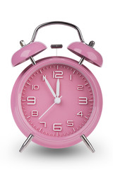 Pink alarm clock with hands at 5 minutes till 12