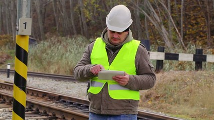 Railway engineer on rails working with tablet PC