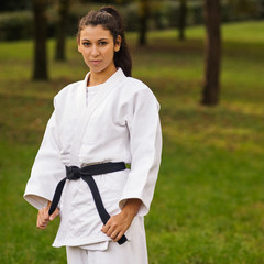 Young caucasian woman practicing judo outdoors in a park.