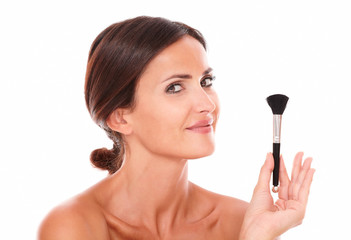 Young woman with make up brush showing her purity
