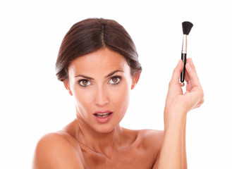 Woman with make up brush for pampering her face