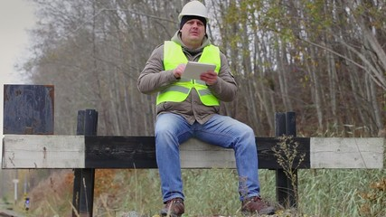 Worker with tablet PC  on the barrier