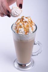 Женская рука кладёт украшение на кофе