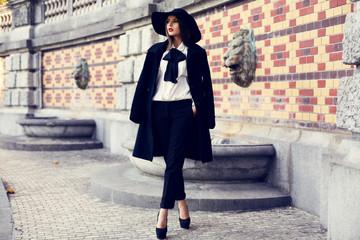 beautiful ladylike woman in coat and felt hat posing at park