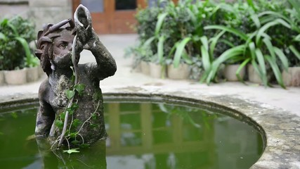 Small old sculpture in a fountain from a traditional garden in S