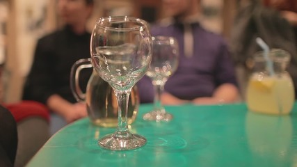 White wine pouring into glass on a turuoise table