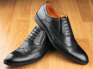 Classic men's shoes stand on the wooden floor