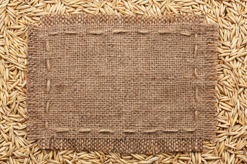 Frame of burlap  lying on a oats  background