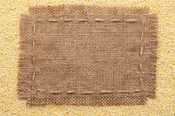 Frame of burlap  lying on a millet  background