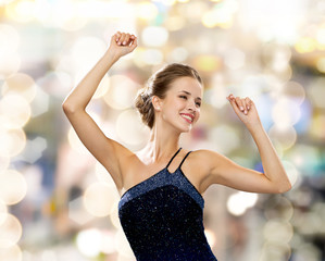 smiling woman dancing with raised hands