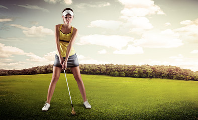 Female golfer with golf club teeing-off on the nature