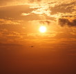 Sun and sunset sky with airplane before landing