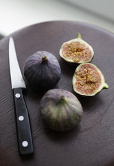 Fresh ripe figs with knife on the wooden table