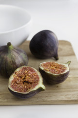 Halved ripe fig on the wooden board with white ceramic bowl