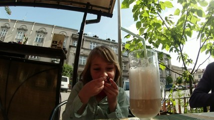 little girl is drinking cocoa through a straw from a large glass