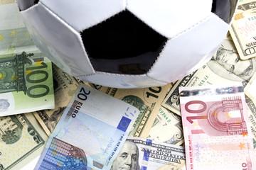 soccer ball on heap of money