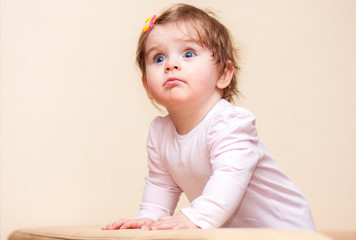 little girl stands near the sofa at home.