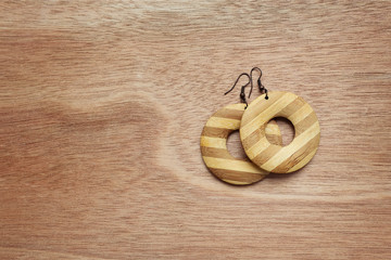 Fashion earrings on wooden surface