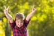 Junge im Karohemd vor buntem Blätterbokeh
