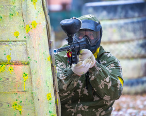 Man in camouflage with paintball gun behind fortification