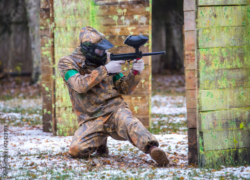 Extreme sportsman playing paintball game on first snow - 72423938