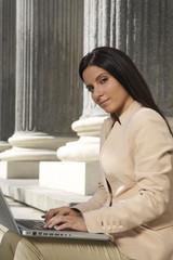 pretty brunette businesswoman typing in laptop