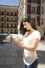 brunette woman with tablet urban background in Madrid city Spain