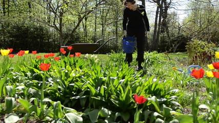 Tired gardener girl weeding flower bed in spring