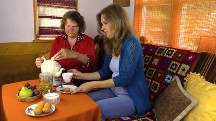grandma poured tea from porcelain tea his pregnant granddaughter