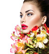 High fashion model girl with colorful flowers and red lips