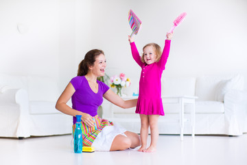 Young mother and daughter sweeping the floor